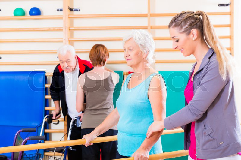 Seniors in physical rehabilitation therapy with trainer, stock photo