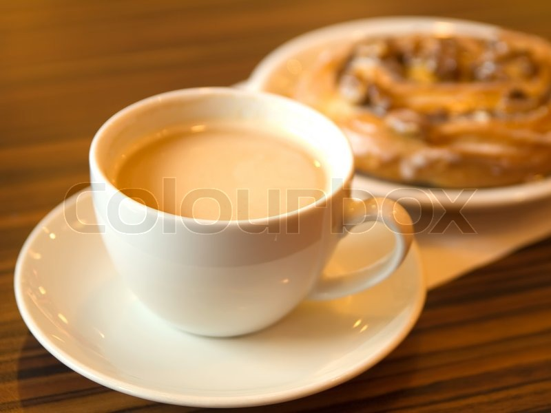 Morning coffee and cinnamon roll in cafe, stock photo