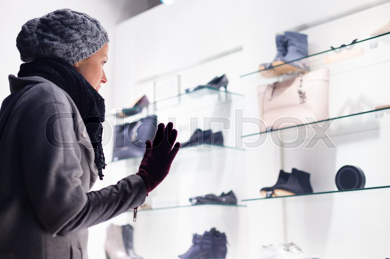 casualy winter dressed lady window shopping in front of sinfully