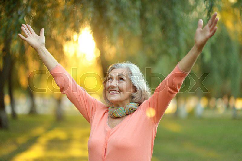 Senior woman walking in the park in autumn, stock photo