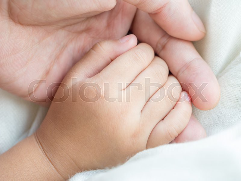 Parent and daughter holding hand together in concept of taking care of the little child, stock photo