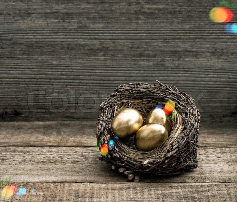 Golden easter eggs in nest on vintage     | Stock image