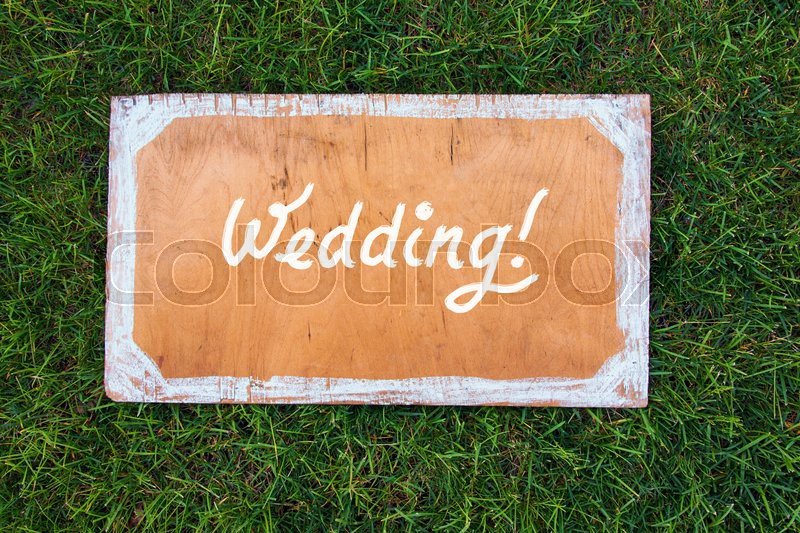 Wedding wooden sign on the grass. Spring or summer theme for ads, stock photo