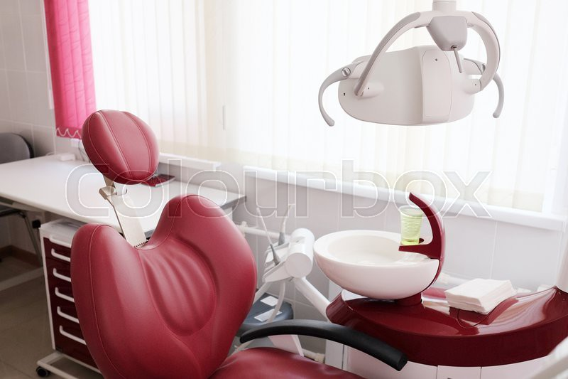 Dental clinic interior design with red chair and tools, stock photo