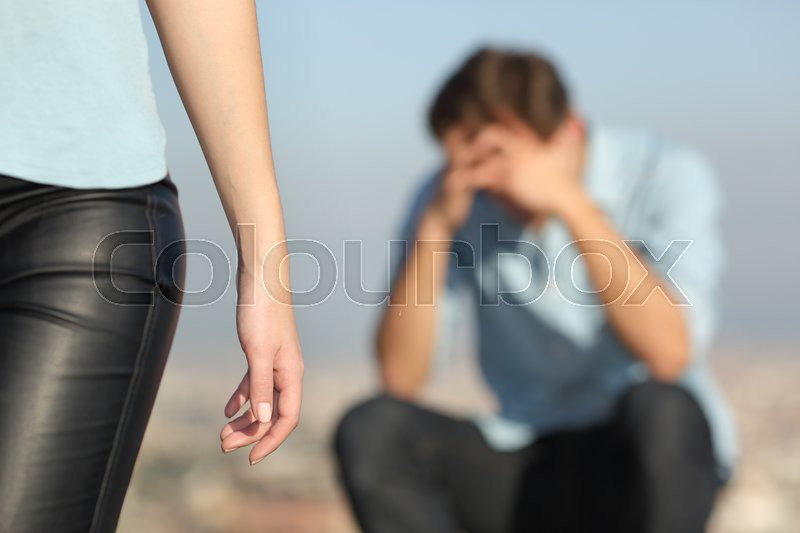 Breakup of a couple with a sad man in the background and the girlfriend leaving him in the foreground, stock photo