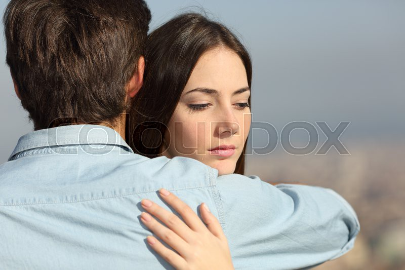 Sad woman hugging her boyfriend and looking down couple problems concept, stock photo