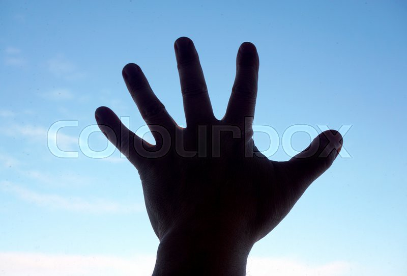 Silhouette of human hand on sky background, stock photo