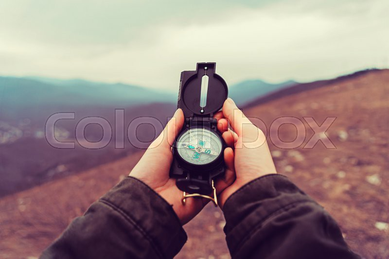 Hiker woman searching direction with a compass in the mountains. Point of view shot, stock photo