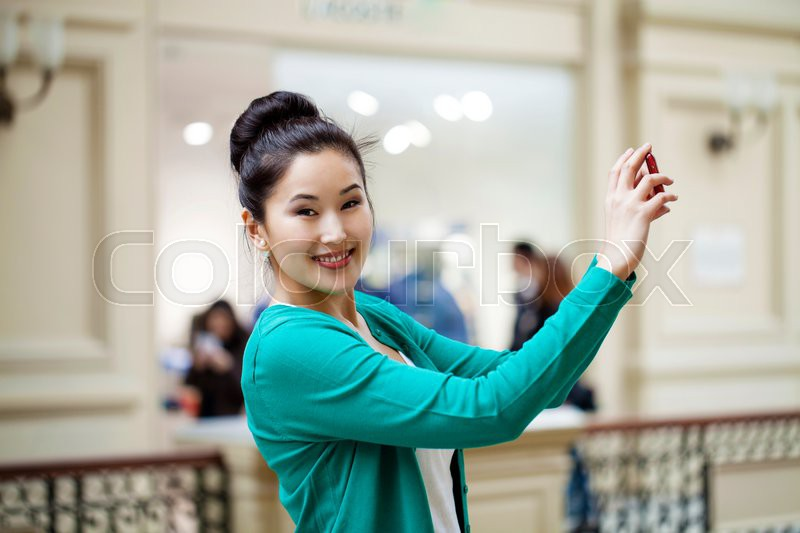 Stock image of 'Young beautiful asian woman tourist taking pictures on mobile phone in Moscow Shop'