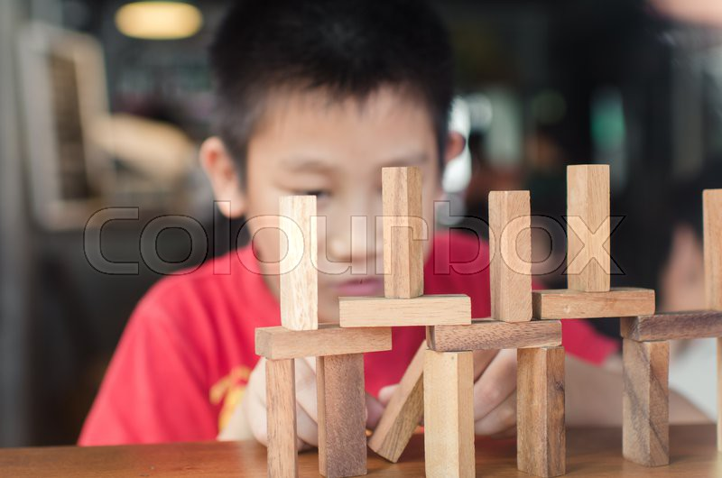 Asian boy playing with the wood game (jenga). Selective focus, stock photo