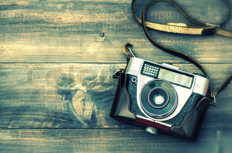 Vintage style photography  Old film camera on wooden background. Top view. Vintage style toned ...