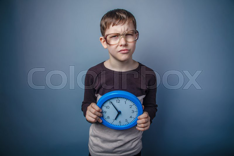 Teenager boy of European appearance with glasses holding a clock on a blue gray background, suspicion, stock photo