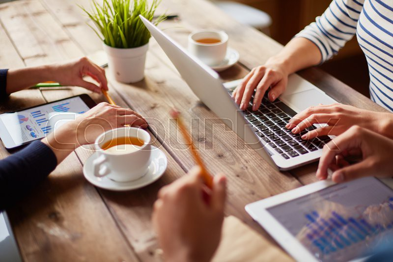 People using different devices at one table, stock photo