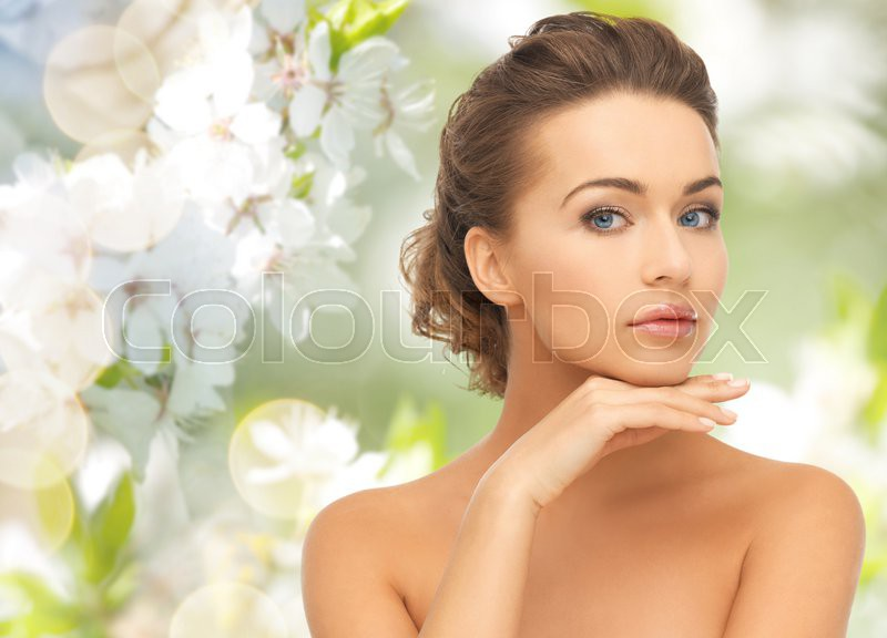 Beauty, people, summer, spring and health concept - beautiful young woman touching her face over green blooming garden background, stock photo
