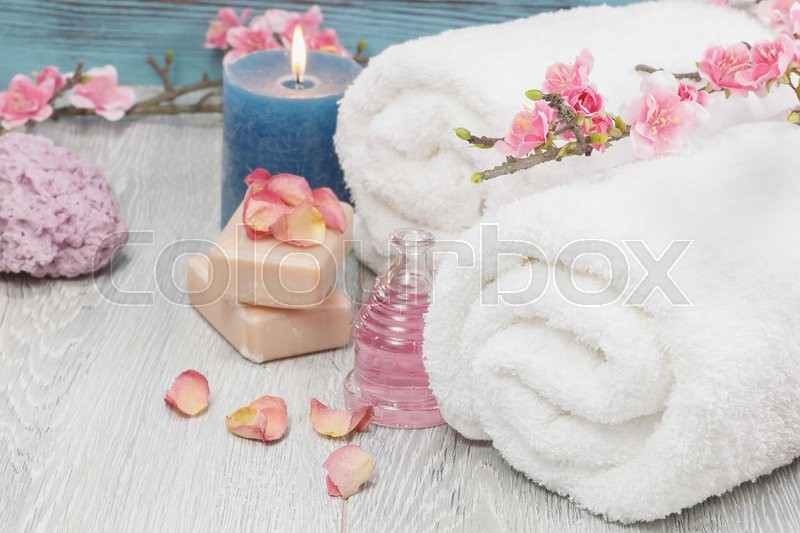 Spa and wellness setting with rose petals, natural soap, candle and towel, stock photo