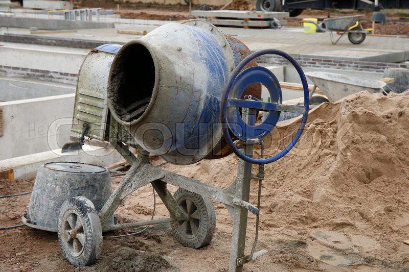 A Concrete Mixer And And A Wheelbarrow At A Construction