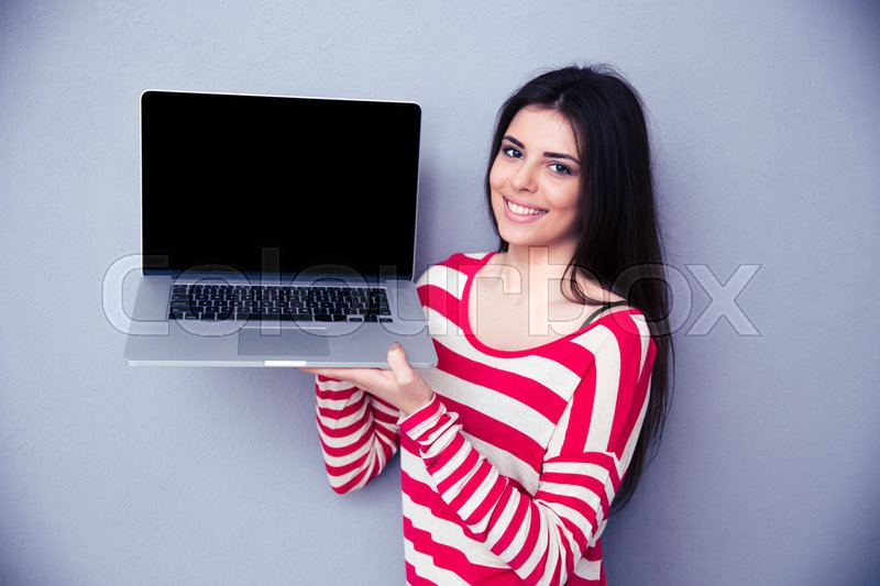 Smiling woman showing blank laptop display over gray background. Looking at camera, stock photo