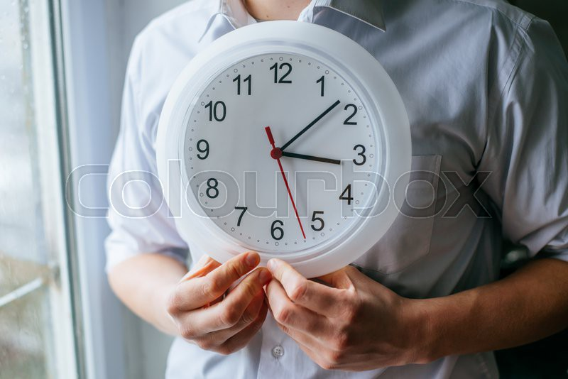 Man holding a clock in the office, stock photo