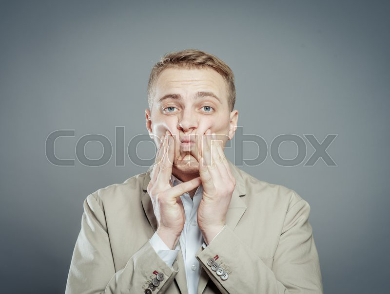Closeup portrait of unhappy, upset, sad thoughtful young business man thinking deeply, bothered by mistakes, hands on face and cheeks, isolated on gray background. Negative, funny emotion facial expressions, stock photo