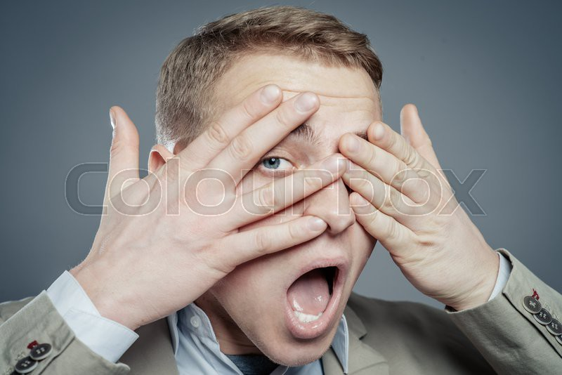 Expressions. Handsome young man in suit feeling fear with open mouth and closing eyes with hands, stock photo