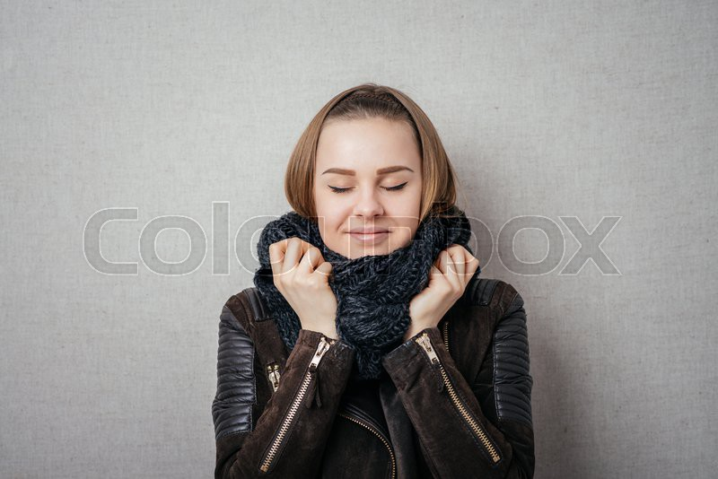 It is so cold. Frozen young women covering face with turtleneck while standing against grey background, stock photo