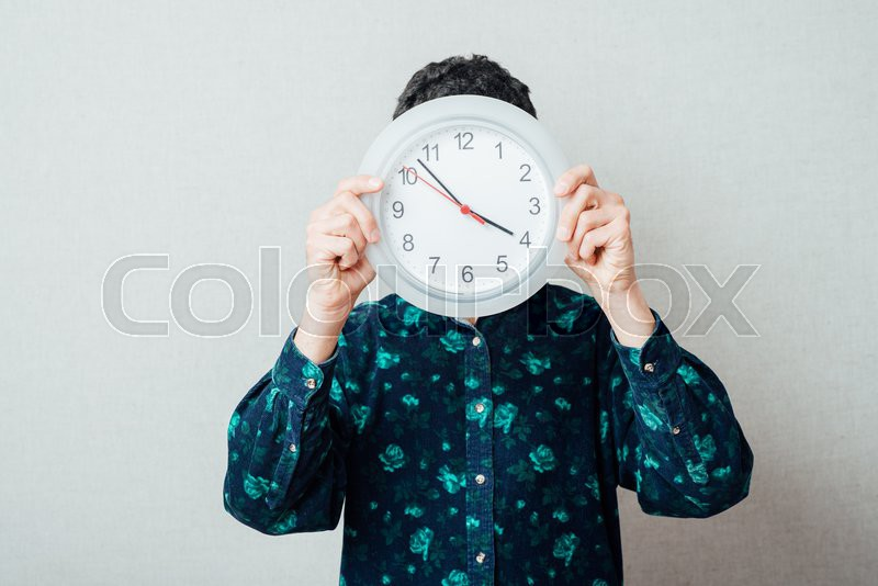 Stock image of 'Man hand holding large office wall clock showing time'
