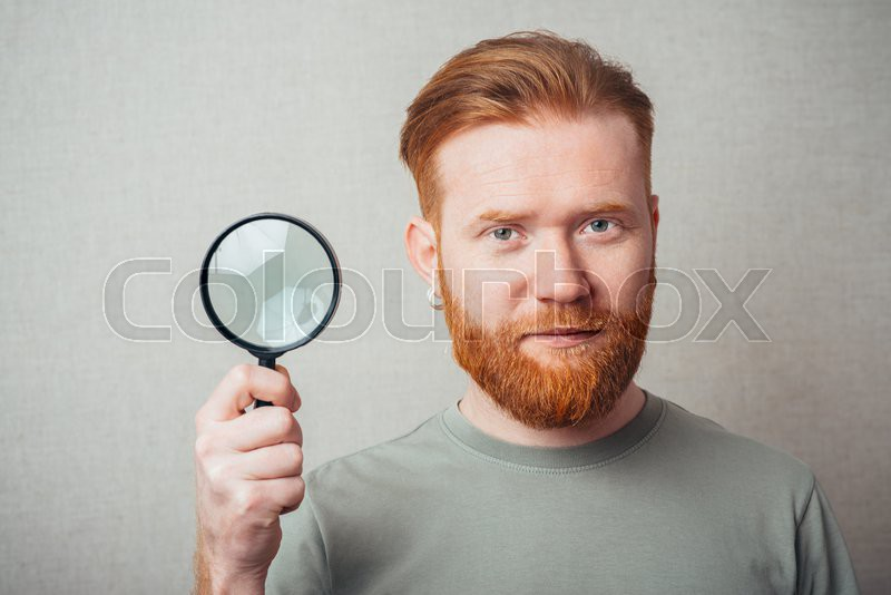 Young hipster red bearded man with magnifying glass, stock photo