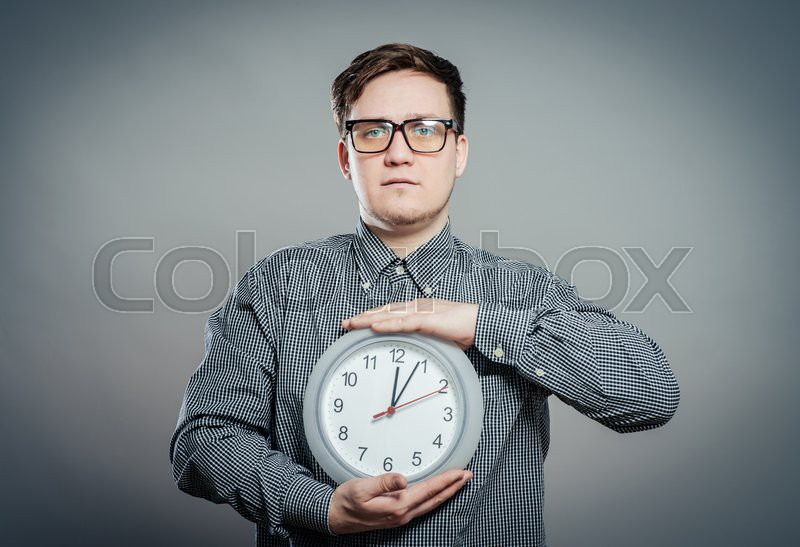 Young Man Holding A Clock On Gray Background, stock photo