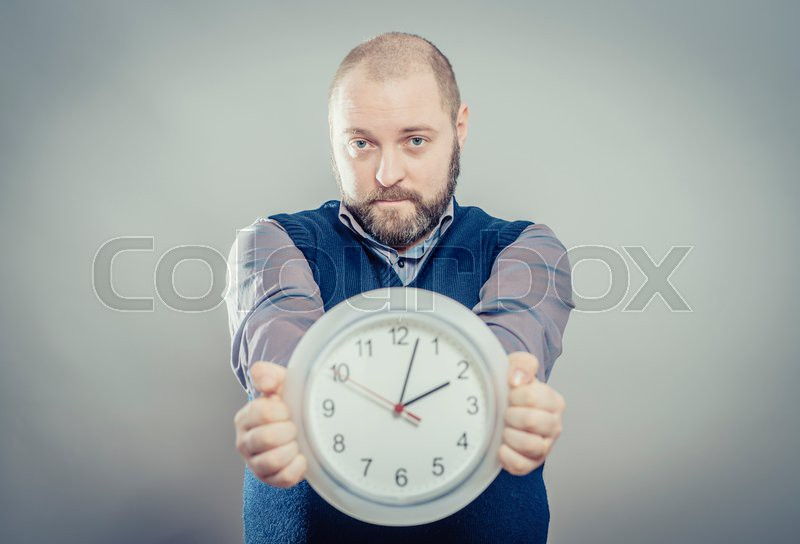 Portrait Of A Young Man Holding A Clock On Gray Background, stock photo