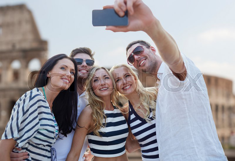 Summer, europe, tourism, technology and people concept - group of smiling friends taking selfie with smartphone over coliseum background, stock photo