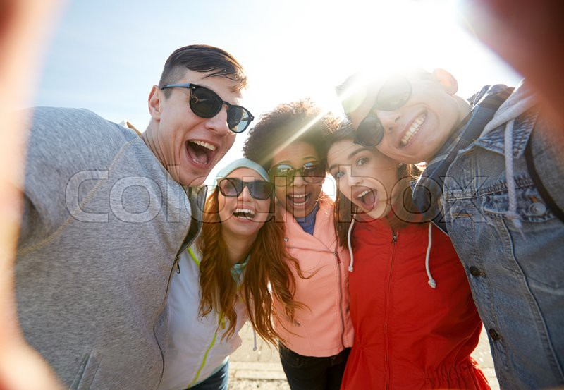 Tourism, travel, people, leisure and technology concept - group of happy laughing teenage friends taking selfie outdoors, stock photo