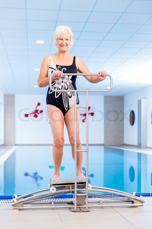 Senior Woman In Underwater Gymnastics Therapy With Sliding Machine