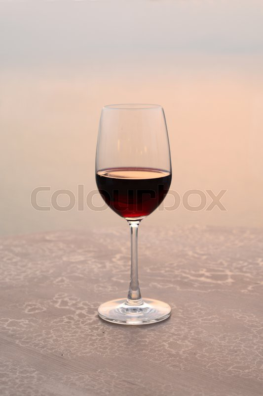 Stock image of 'Glass of wine at sunset on the sea'