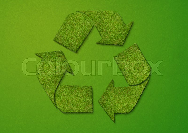 A recycling sign made of grass on a green textured background, stock photo
