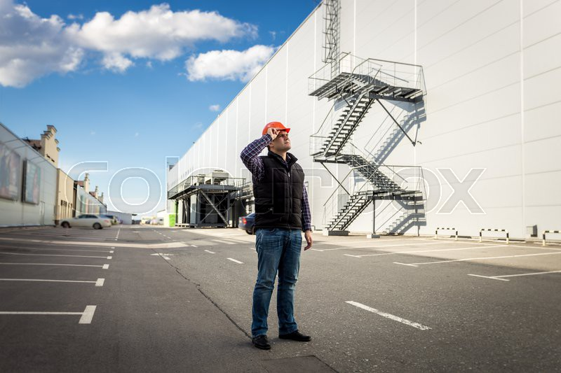 Full length portrait of male worker posing on parking of industrial building, stock photo