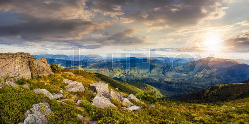 Panoranic mountain landscape. valley with stones in grass on top of the hillside of mountain range in sunset light, stock photo