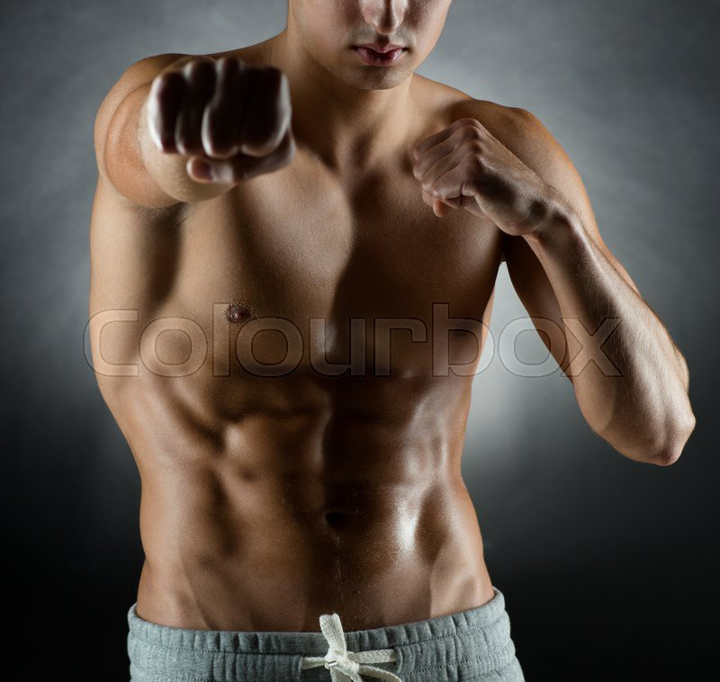 Sport, bodybuilding, strength and people concept - young man in fighting stand over black background, stock photo