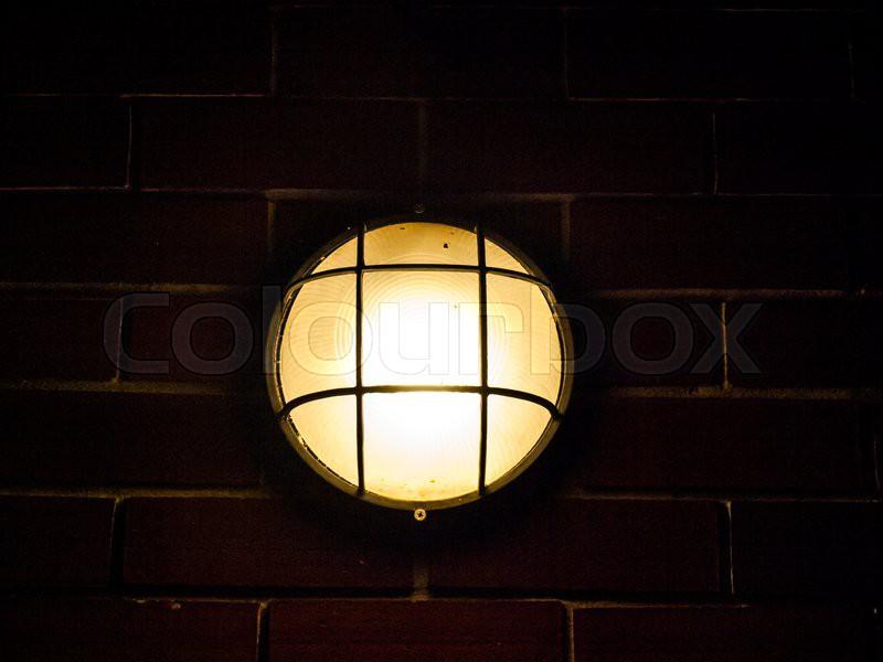 Turn on outdoor lamp on brick wall, stock photo
