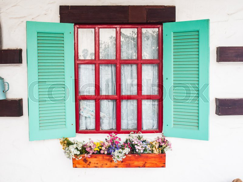 Opened wooden shutter light green window on white wall with flower bed, stock photo