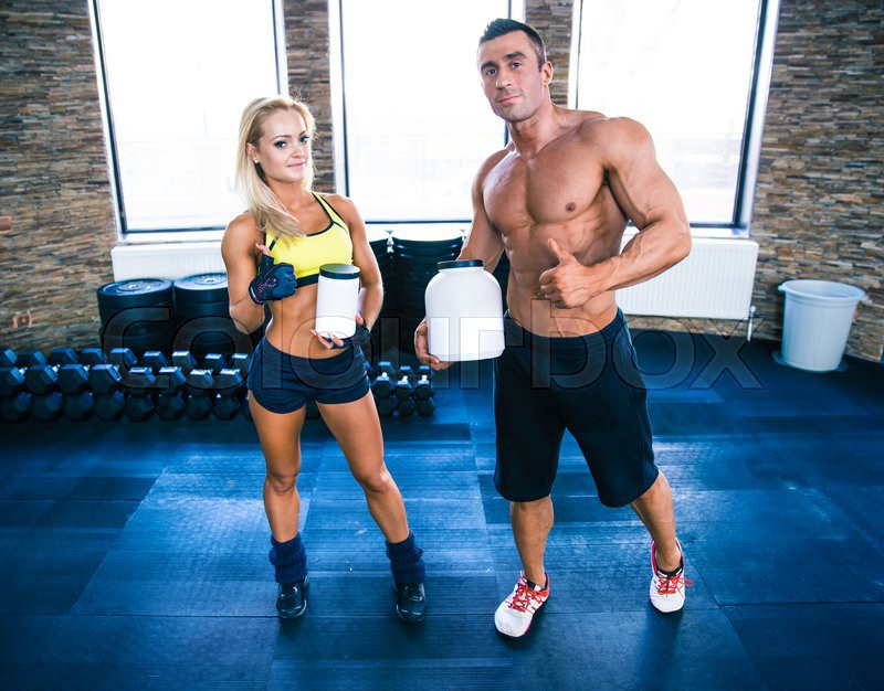 Muscular man and sporty woman holding container with sports nutrition and showing thumbs up in gym, stock photo