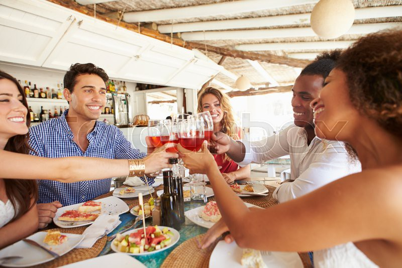 Group Of Young Friends Enjoying Meal In Outdoor Restaurant, stock photo