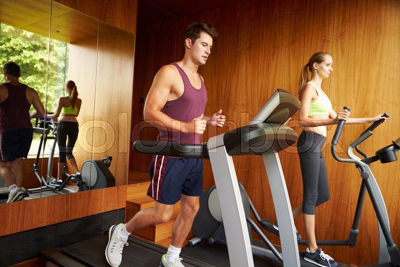 Couple exercising together in home gym stock photo colourbox
