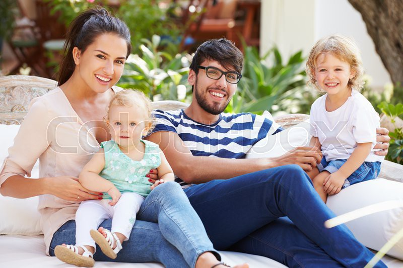 Family Sitting Outdoors In Garden At Home Together, stock photo