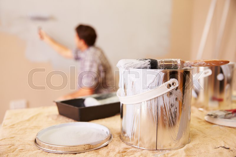 Man Decorating Room Using Paint Roller On Wall, stock photo