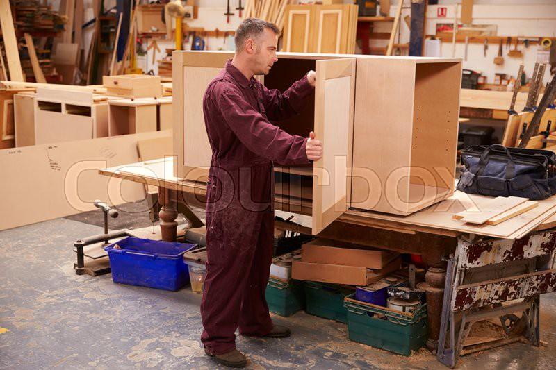 Carpenter Building Furniture In Workshop, stock photo
