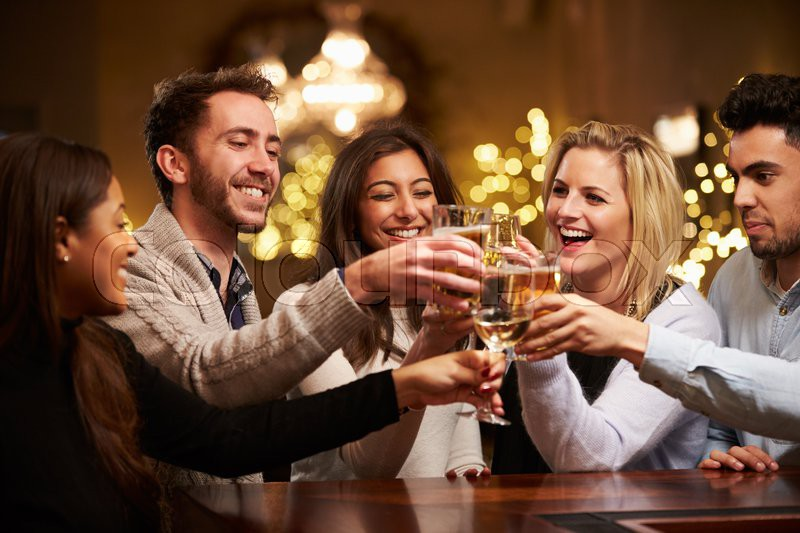 Group Of Friends Enjoying Evening Drinks In Bar, stock photo