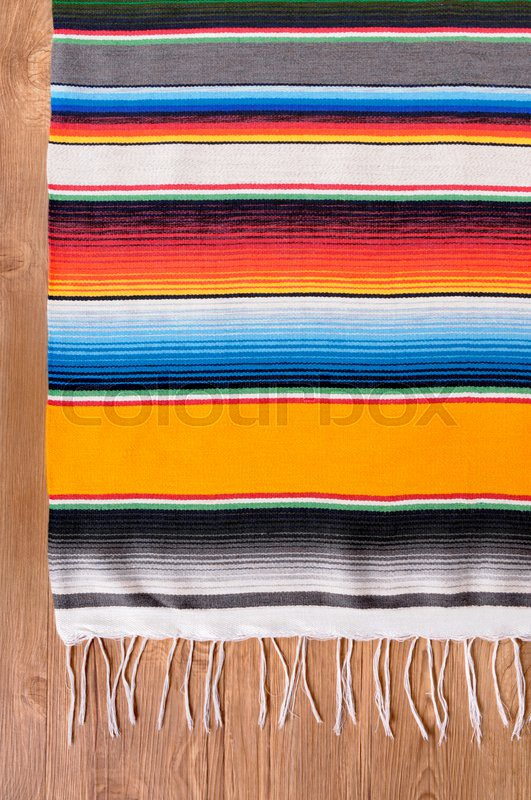 Mexican background with traditional serape blanket or rug on a wood floor. Space for copy, stock photo