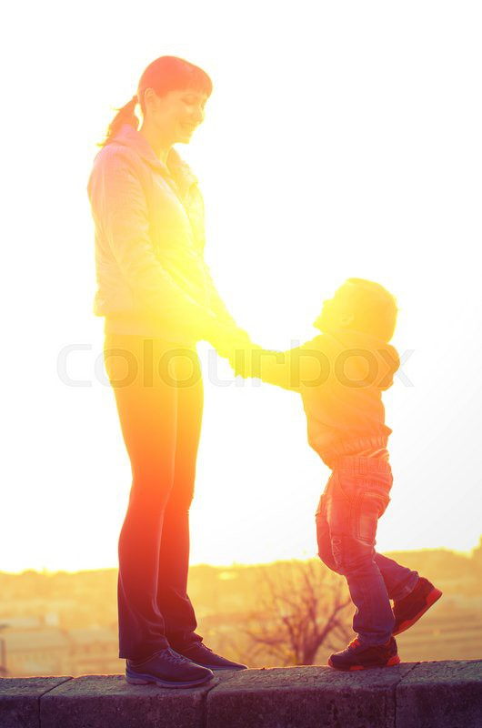 Young mother and son holding hands and laughing standing on the parapet on the background of the backlight. Family Vintage composition, stock photo