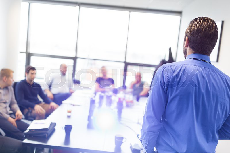 Business man making a presentation at office. Business executive delivering a presentation to his colleagues during meeting or in-house business training, explaining business plans to his employees, stock photo