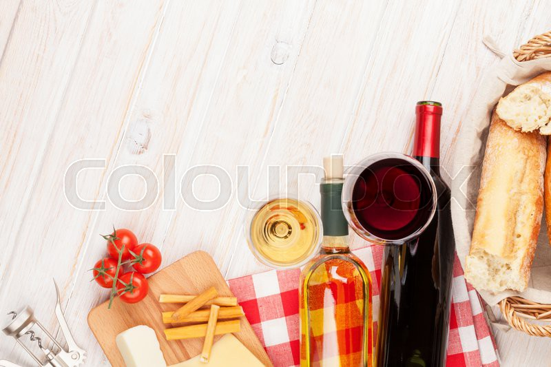 White and red wine, cheese and bread on white wooden table background. Top view with copy space, stock photo